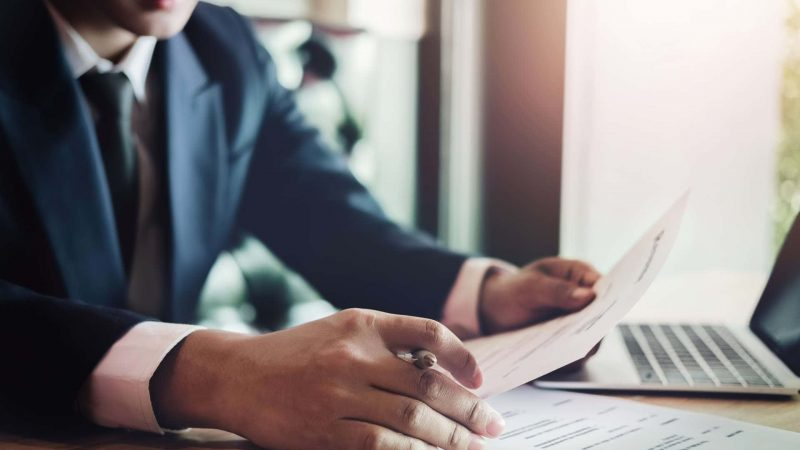 Businessman completing employment screening paperwork