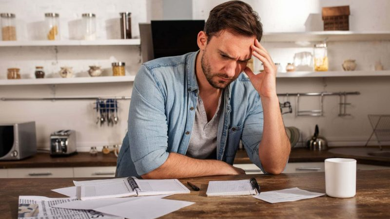 Distressed looking man at kitchen island with financial paperwork