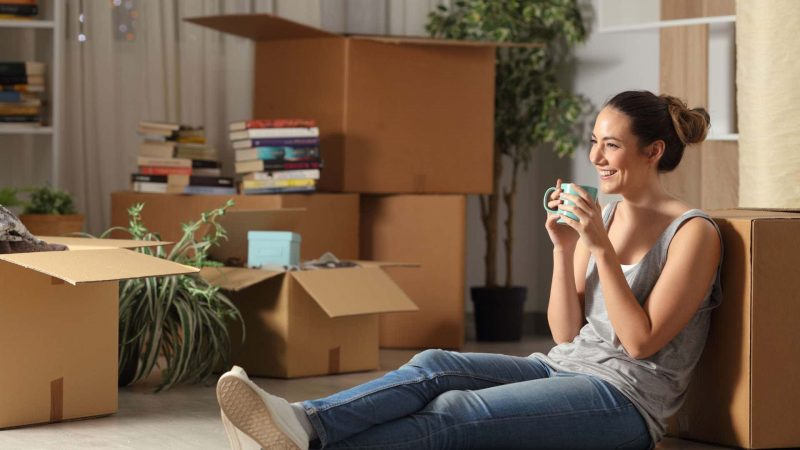 Smiling young woman sitting on floor surrounded by moving boxes