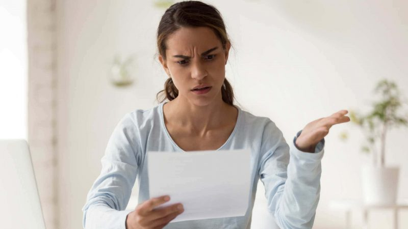 Woman looking exasperated holding up sheet of paper