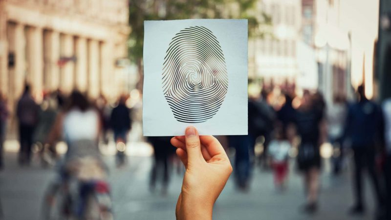 hand holding large fingerprint image in front of blurred out crowd